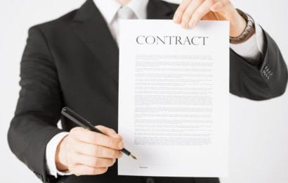 man-in-suit-holding-contract-paper